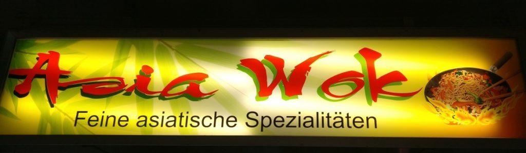 """Moderne Mainzer Wände: Leuchtreklame führt das Auge, läßt kein Verweilen auf kahlen Flächen zu. Das Asia Wok am Südbahnhof. Pardon: Bahnhof """"Mainz, römisches Theater"""""""