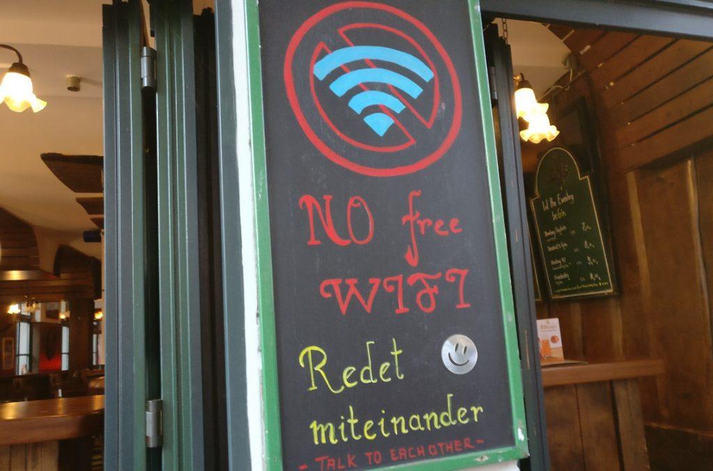 """Mainzer Wände zeugen auch von der Mainzer Lebensart. """"NO WIFI: Redet miteinander"""" fordert die Tafel an der Wand am l'Arcade.  So ist der Mainzer: Er redet, statt zu whatsappen. Jedenfalls die meisten."""