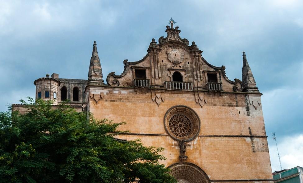Die Kirche San Miguel ist eine weitere bemerkenswerte Kirche in Felanitx. Wie euch wahrscheinlich schon aufgefallen ist, hat es uns der kleine Ort nahe der Küste besonders angetan.  Unweit des Glückshotel Mallorca gelegen, ist er uns am Sonntag Zufluchtsort und sorgt sich nicht zuletzt um unser leibliches Wohl. Verwunderlich: gerade in diesem Ort mit seinen zahlreichen Kirchen herrscht gerade am andächtigen Sonntag auf dem großen Wochenmarkt quirliges und weltliches Treiben. (#2)